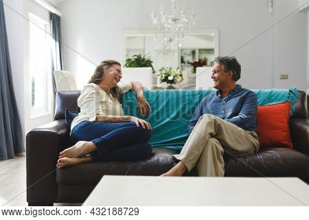 Happy senior caucasian couple in living room sitting on sofa, talking. retirement lifestyle, spending time at home.