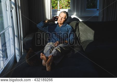 Senior caucasian man in living room sitting on sofa, talking on smartphone. retirement lifestyle, spending time at home with technology.