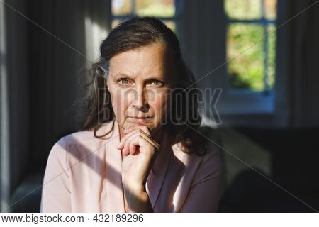 Portrait of thoughtful senior caucasian woman in bedroom, looking to camera. retirement lifestyle, spending time alone at home.