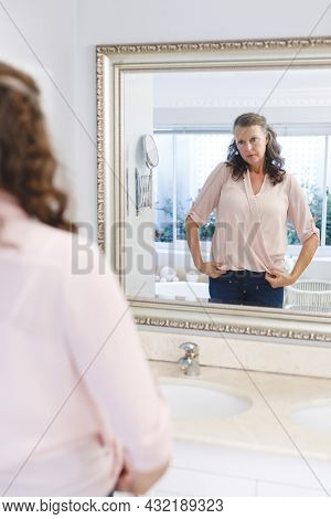 Senior caucasian woman in bathroom, looking at herself in mirror. senior caucasian woman in bathroom, looking at her face in mirror. retirement lifestyle and the aging process.