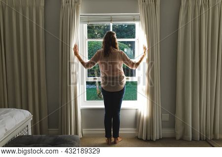 Thoughtful senior caucasian woman in bedroom, standing next to window, opening curtains. retirement lifestyle, spending time alone at home.