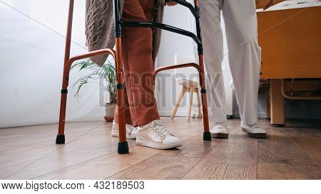 Partial View Of Senior Woman Stepping With Walkers Near Nurse