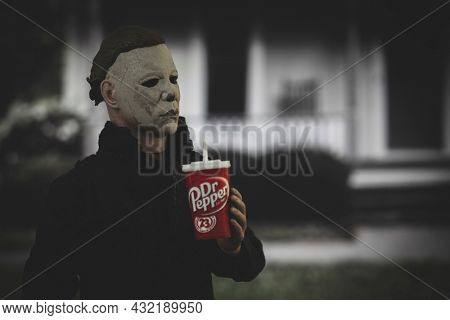 SEPT 3 2021: Halloween slasher Michael Myers drinking Dr Pepper soda in front of the Myers house in Haddonfield  - Neca action figure