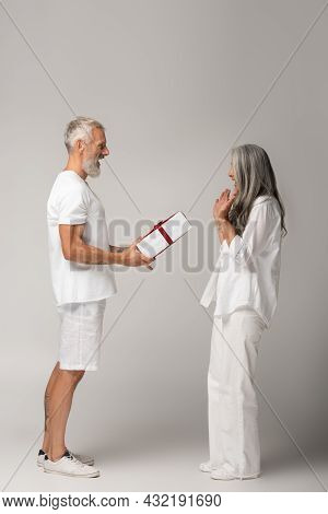 Full Length Of Happy Middle Aged Man Giving Wrapped Gift Box To Amazed Asian Wife On Grey