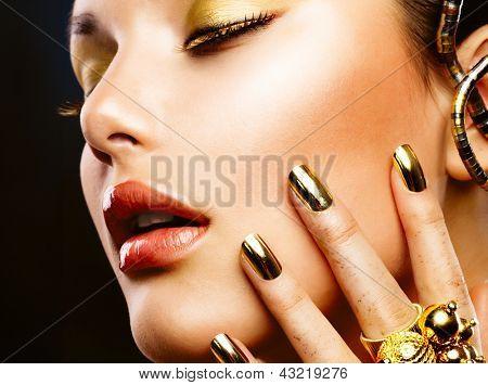 Fashion Girl Portrait. Gold Makeup. Golden nails and Eyeshadows. Golden Make-up and Nailpolish