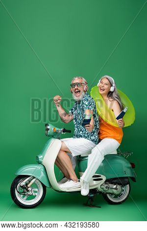 Multiethnic And Middle Aged Couple In Wireless Headphones Holding Passports With Air Tickets And Rid