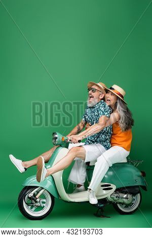 Scared And Multiethnic Middle Aged Couple In Sun Hats Riding Moped On Green