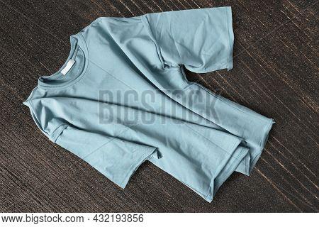 Blue Basic T-shirt On Dark Brown Wood Background