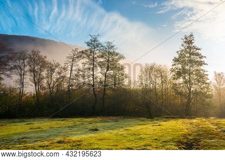 Countryside Scenery At Sunrise. Fog Glowing In Morning Light Above The Forest On The Grassy Meadow.