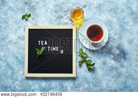 Tea Time. Black Letter Board With Text On Blue Table With Glass Cup Of Tea With Mint Leaves