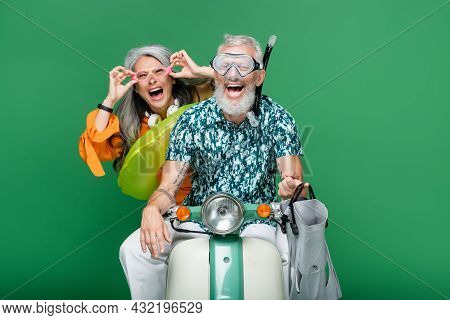 Multiethnic And Excited Middle Aged Couple In Goggles Riding Moped Isolated On Green