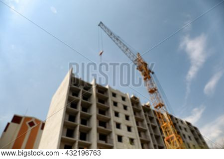 Blurred View Of Unfinished Building And Construction Crane Outdoors