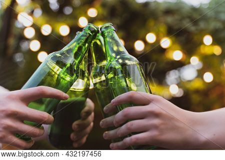 Friends Clink On Bottles Of Beer. Outdoor Party With Alcohol. Fun And Celebration. Birthday Toast