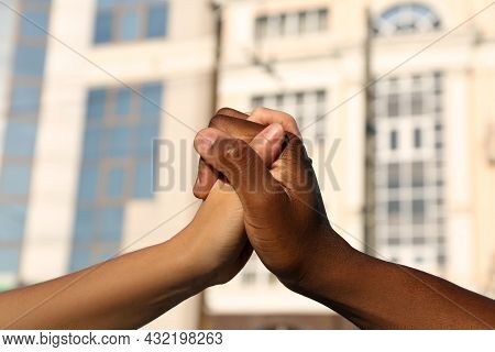 Woman And African American Man Clasping Hands On City Street, Closeup