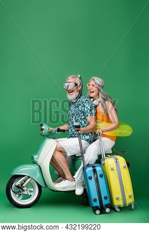Excited And Multiethnic Middle Aged Couple In Goggles Holding Passports And Luggage While Riding Mot