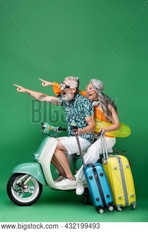 Amazed And Multiethnic Middle Aged Couple In Goggles Pointing With Fingers And Holding Passports Whi