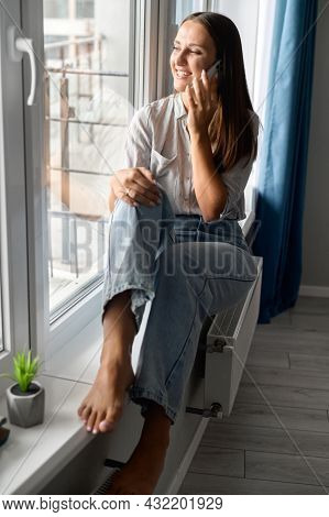 Vertical Portrait Of Charming Woman Talking On The Smartphone Sitting On The Window Cill At Home. Sm