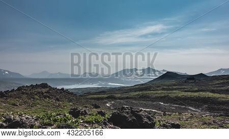 Scant Vegetation And Volcanic Rocks Are Visible On The Mountain Slope. In The Distance, You Can See