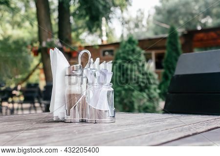 Paper Napkins, Pepper And Toothpicks In Metal Stand On Table In Cafe. Summer Terrace. Lunch In Fresh