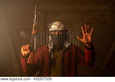 Militant Or Gangster With Face Cover And Gun In Hand Surrendering By Putting Hands Up