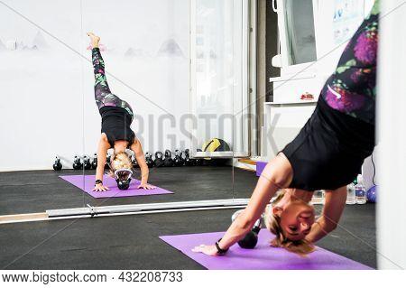 Adult Woman Is Practicing Yoga In Gym. Eka Pada Adho Mukha Svanasana/one-legged Downward-facing Dog