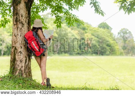 Women Hiker Or Traveler With Backpack Adventure Holding Map To Find Directions And Relax In The Jung
