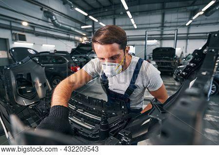 Automotive Technician Inspecting Detail Of A Car