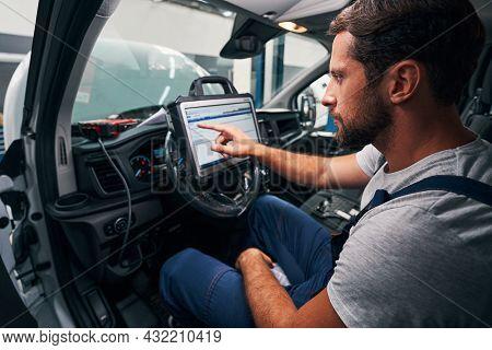 Auto Mechanic Providing Car Diagnostics In Cabin