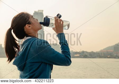 Thirsty Young Woman Runner Is Resting And Drinking Water Bottle After Morning Cardio On Street Outdo