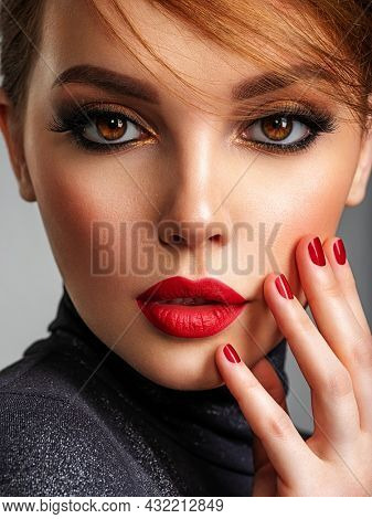 Beautiful brunette girl with red lips and short hair. Pretty young sensual woman with red nails. Closeup portrait of a model with bright makeup on a face. Attractive female posing at studio.