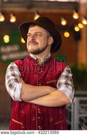 Caucasian Bearded Man, Owner Of Restaurant In Traditional Bavarian Festive Costume Greeting Customer