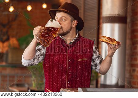 Portrait Of Happy Bearded Man In Traditional Bavarian Festive Costume, Hat And Red Vest Tasting Beer