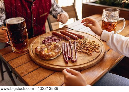 Close-up Male Hand With Beer Snacks And Beer Glasses During Oktoberfest Holiday Meeting. Traditions,