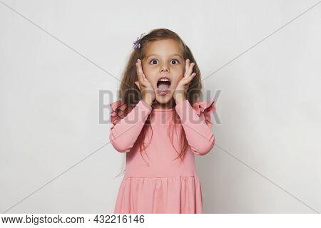 Portrait Of Surprised Little Girl Against White Background