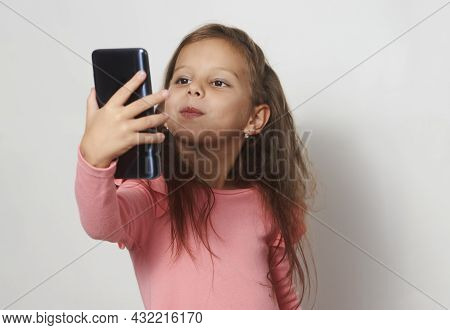 Portrait Of A Little Girl Using Cell Phone Against White Background