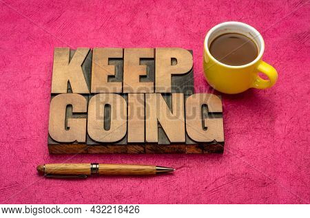 Keep going motivation word abstract in vintage letterpress wood type blocks with a cup of coffee, determination, persistence and tenacity concept