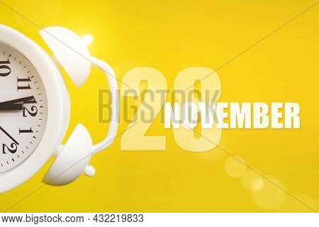 November 28th. Day 28 Of Month, Calendar Date. White Alarm Clock On Yellow Background With Calendar