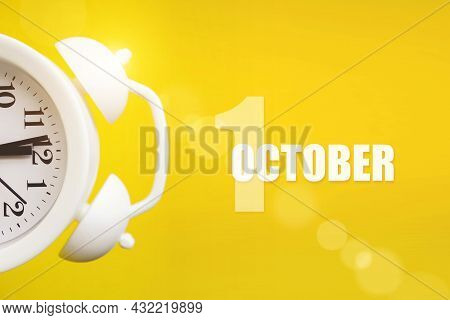 October 1st . Day 1 Of Month, Calendar Date. White Alarm Clock On Yellow Background With Calendar Da