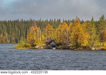 Finnish autumn landscape with lake country house. Beautiful colorful ruska season in Finland. Autumn forest with a lakeside cottage in Finland