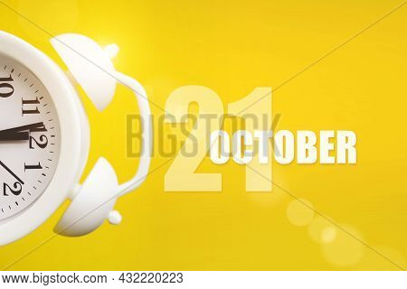 October 21st . Day 21 Of Month, Calendar Date. White Alarm Clock On Yellow Background With Calendar