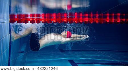 At Start. Sportive Male Swimmer In Red Cap And Goggles In Motion And Action During Training At Pool,