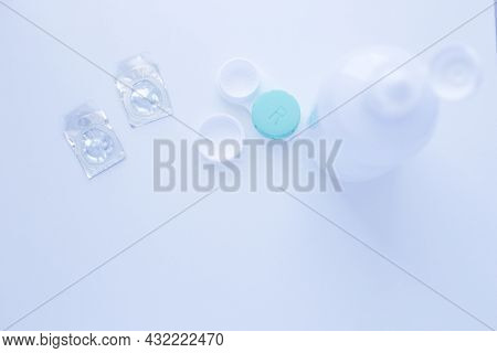 A Lens Remover, A Lens Storage Container And Two Contact Lenses Lie On Top Of The Photo On A White B