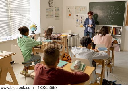 Young teacher standing by blackboard in front of intercultural schoolkids sitting by desks