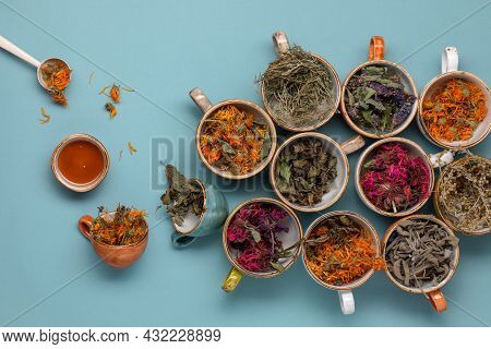 Assortment Of Dried Relaxing Tea Herbs In Colourful Cups On Blue Background With Honey Close Up. Cal