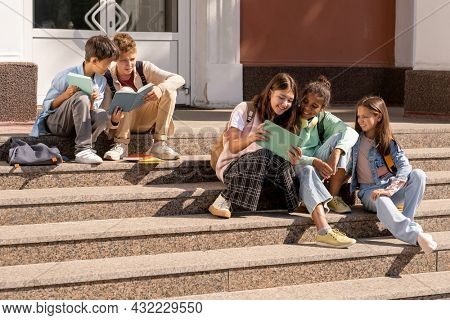 Group of adolescent schoolkids using tablets while sitting on staircase of school building on sunny day