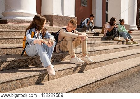 Two schoolkids in casualwear discussing plans for the day while sitting on large staircase