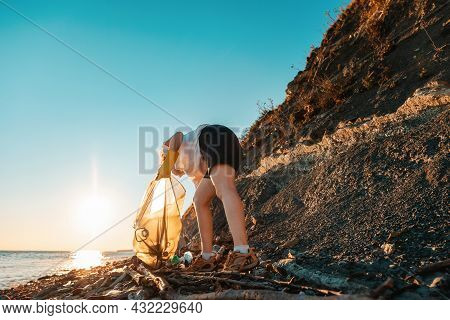 A Volunteer Activist Collects Garbage On A Wild Beach. Copy Space. Cleaning Of The Coastal Zone. The