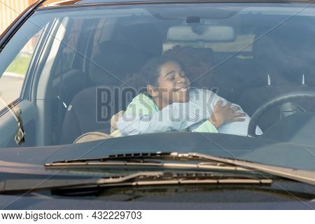Affectionate mom and daughter giving each other goodbye hug in the car before going to school