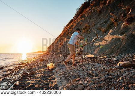 World Environment Day. A Male Activist Is Cleaning Up On A Wild Beach. In The Background, The Sea An