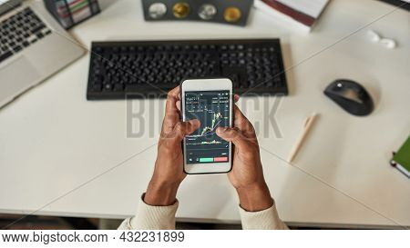 Top View Of Ethnic Male Trader At Home Use Computer Cellphone Analyze Financial Graph Chart On Stock